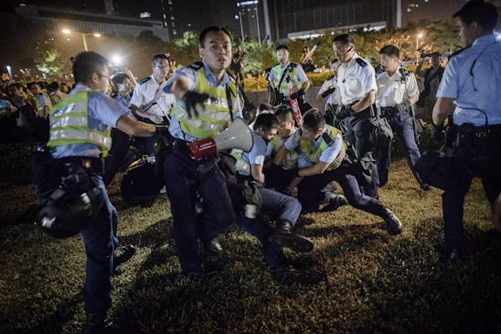 Police forces arrest pro-democracy protesters outside the central government offices in Hong Kong on October 14, 2014 (AFP Photo/Philippe Lopez)