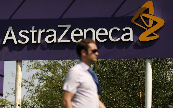 A man walks past a sign at an AstraZeneca site in Macclesfield - Reuters