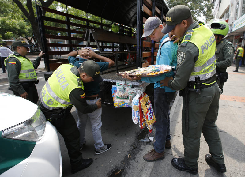 FILE - In this Feb. 22, 2018 file photo, Colombian police officers detain Venezuelan migrants who do not have no ID's and permits to sell products, in Cucuta, Colombia. Officially, Colombia deports few Venezuelan migrants: 442 have been removed from the country so far in 2018, according to government figures. (AP Photo/Fernando Vergara, File)