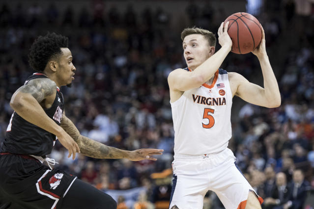 Virginia guard Kyle Guy (5) looks for a teammate as Gardner-Webb guard David Efianayi, left, defends during a first-round game in the NCAA mens college basketball tournament Friday, March 22, 2019, in Columbia, S.C. (AP Photo/Sean Rayford)