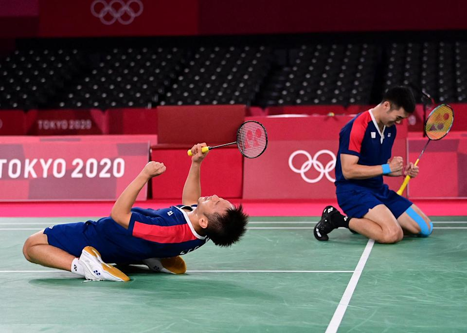 <p>Taiwan's Lee Yang (left) and Wang Chi-lin celebrate winning their July 30 men's doubles badminton semi-final match against Indonesia.</p>