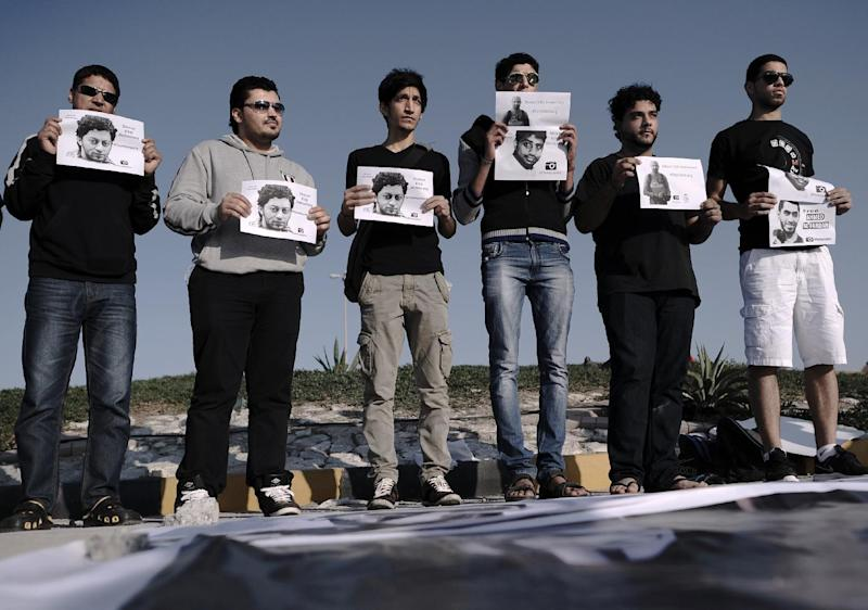 Bahraini protestors show portraits of Hussain Hubail and other jailed Bahraini photographers Ahmed Humaidan,  Hasan Matooq and Ahmed al-Fardan during an anti-government protest in the village of Shakhora, west of Manama, on January 3, 2014