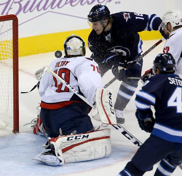 Washington Capitals goaltender Braden Holtby (70) stops Winnipeg Jets' Bryan Little (18) during the third period of an NHL hockey game in Winnipeg, Manitoba, Tuesday, Oct. 22, 2013. (AP Photo/The Canadian Press, Trevor Hagan)