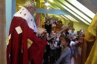 Bookseller Jaromir Vytopil, left, appoints the youngest schoolchildren to the order of readers at a library in Pelhrimov, Czech Republic, Thursday, Feb. 7, 2020. Some 25,000 have been killed by COVID-19 in the hard-hit Czech Republic. Jaromir Vytopil was one of them. His everyday presence in the small Czech town of Pelhrimov was something everybody took for granted for seven decades as he had served the generations of readers. The longest serving Czech bookseller, passed away on Nov 9. 2020, at age of 83. (AP Photo/Miroslav Krsek)