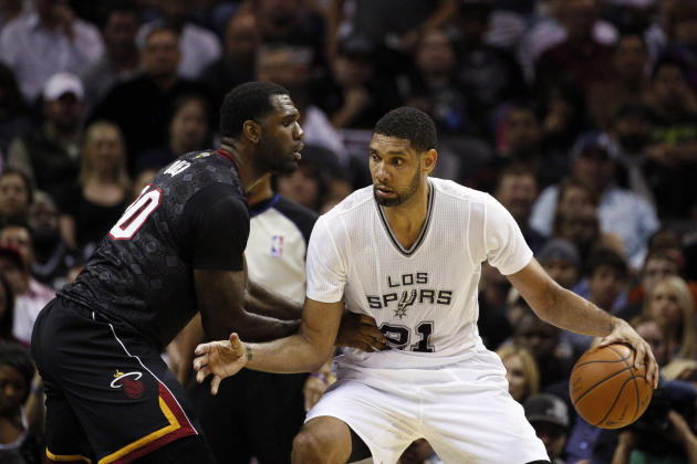 Mar 6, 2014; San Antonio, TX, USA; San Antonio Spurs forward Tim Duncan (21) is defended by Miami Heat center Greg Oden (20) during the first half at AT&T Center. (Soobum Im-USA TODAY Sports)
