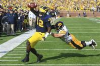 Michigan quarterback Devin Gardner (12) pulls away from Iowa linebacker James Morris (44) for a touchdown during the second quarter of an NCAA college football game at Michigan Stadium in Ann Arbor, Mich., Saturday, Nov. 17, 2012. (AP Photo/Carlos Osorio)