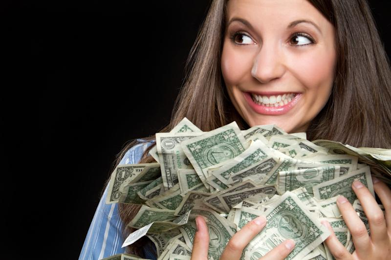 woman smiling and holding a large pile of cash