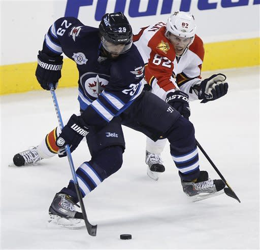 Winnipeg Jets' Johnny Oduya (29) and Florida Panthers' Tomas Kopecky (82) battle for the puck during the second period of NHL hockey game action in Winnipeg, Manitoba, Thursday, Nov. 10, 2011. (AP Photo/The Canadian Press, Trevor Hagan)