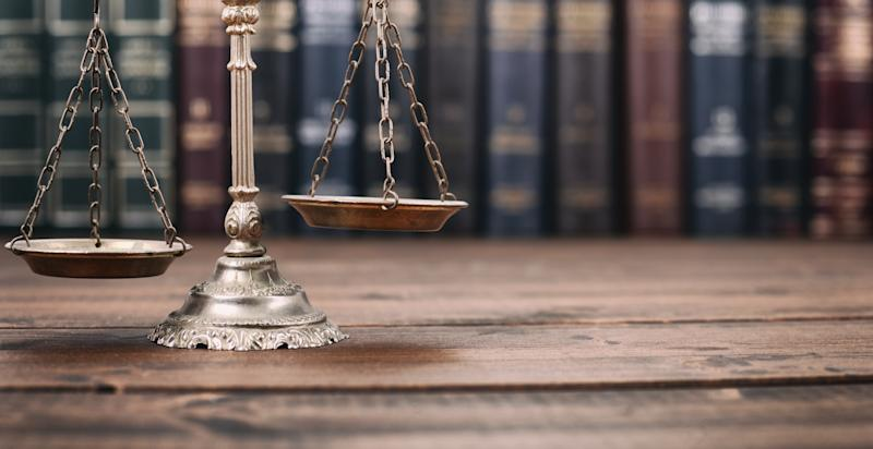 Scales of Justice l on a wooden background, Law library concept. Photo: Getty
