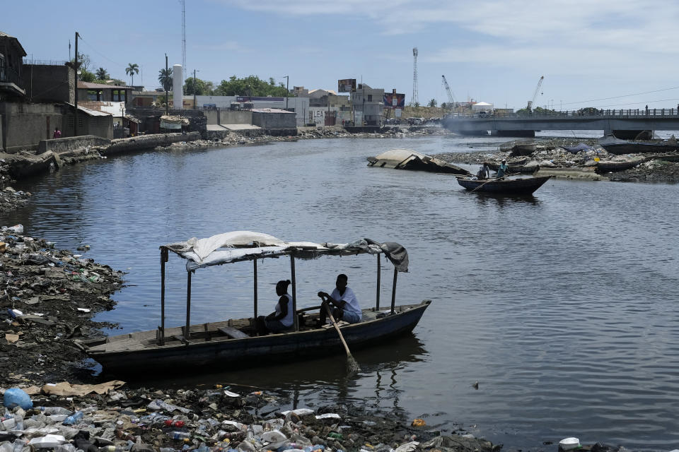 A man waits to row his boat across the river in Cap-Haitien, Haiti, Thursday, July 22, 2021. The city of Cap-Haitien is holding events to honor slain President Jovenel Moïse on Thursday ahead of Friday's funeral. (AP Photo/Matias Delacroix)