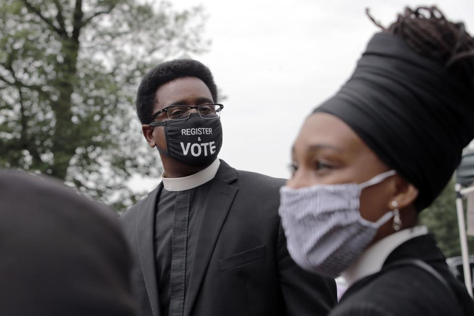 "FILE - In this Monday, July 20, 2020 file photo, the Rev. Rahsaan Hall, of the St. Paul AME Church in Cambridge, Mass., wears a mask which reads, ""Register & Vote"" outside the Statehouse in Boston, on a day when thousands across the country planned to walked off the job to protest systemic racism and economic inequality that has worsened during the coronavirus pandemic. (AP Photo/Charles Krupa)"