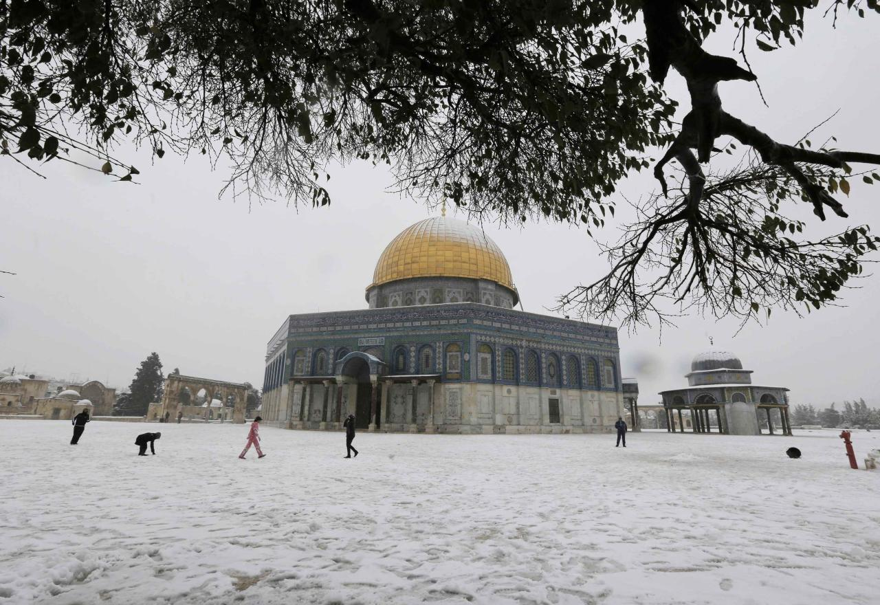 People walk in front of the snow capped Dome of the Rock in the compound known to Muslims as Noble Sanctuary and to Jews as Temple Mount, in Jerusalem's Old City December 12, 2013. Snow fell in Jerusalem and parts of the occupied West Bank where schools and offices were widely closed and public transport was paused. REUTERS/Ammar Awad (JERUSALEM - Tags: RELIGION ENVIRONMENT)