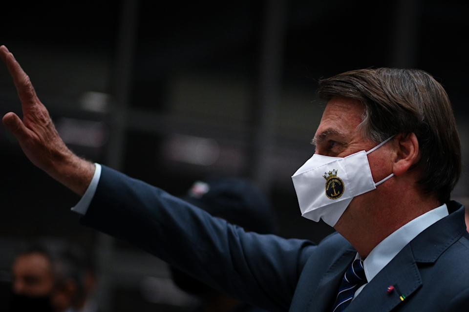 Brazil's President Jair Bolsonaro gestures to supporters wearing a protective face mask before a press conference amidst the Coronavirus (COVID-19) pandemic at Galeao Airport in Rio de Janeiro, Brasil, on May 5, 2021. (Photo by Andre Borges/NurPhoto via Getty Images)