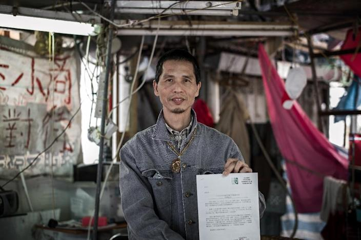 Villager Kwok Yue-ka holds an official notice from the Hong Kong Lands Department asking him to leave his home at Nga Tsin Wai village, which is to be demolished as part of a city re-urbanisation plan (AFP Photo/Philippe Lopez)