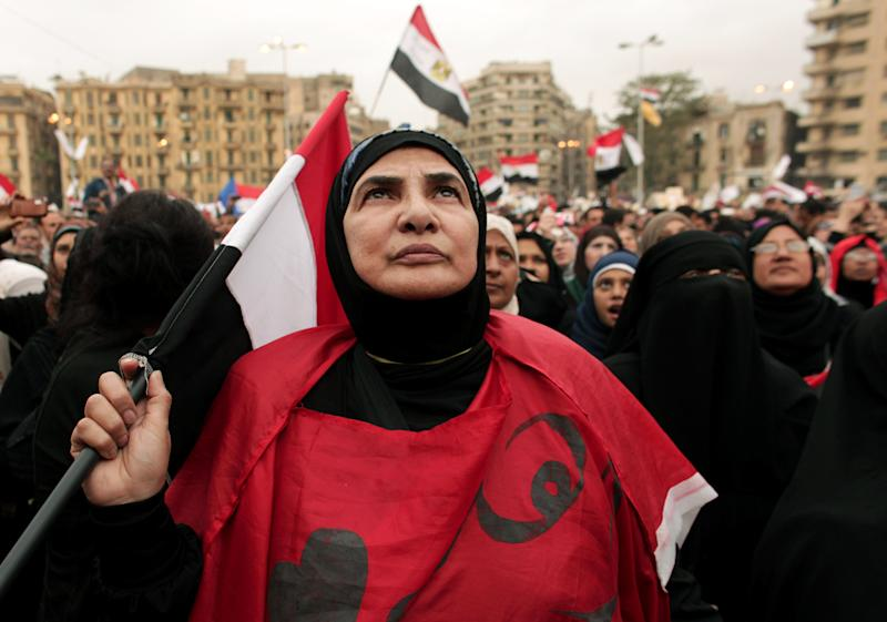 FILE - In this Tuesday, Dec. 4, 2012 file photo, an Egyptian woman holds a national flag as she listens to speakers, not pictured, during a protest calling for the ouster of Islamist President Mohammed Morsi in Tahrir Square in Cairo, Egypt. Women activists say they won a major step forward with Egypt's new constitution, which enshrined greater rights for women. But months after its passage, they're worrying whether those rights will be implemented or will turn out to be merely ink on paper. Men hold an overwhelming lock on decision-making and are doing little to bring equality, activists say, and the increasingly repressive political climate is stifling chances for reforms. (AP Photo/Maya Alleruzzo)