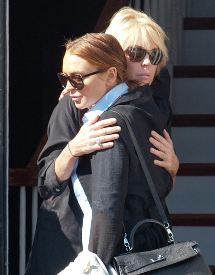 October 10, 2012: Lindsay Lohan gives mom Dina Lohan a hug this morning as she leaves Dina's home in Long Island, New York. The mother and daughter pair were involved in a huge blowout in the early morning hours with police rushing to the scene. The pair were reportedly returning from a NYC nightclub at around 4am when they began arguing. Things reportedly got violent when they got back to the house and Lindsay is said to have sustained a cut on her leg.