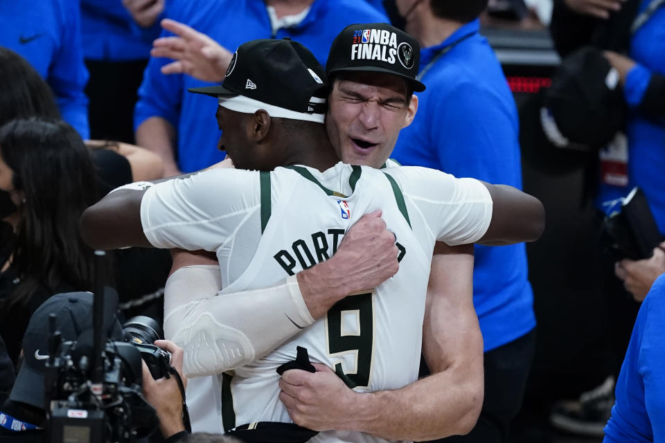 Milwaukee Bucks' Brook Lopez, right, hugs Bobby Portis after defeating the Atlanta Hawks in Game 6 of the Eastern Conference finals in the NBA basketball playoffs and advancing to the NBA Championship, Saturday, July 3, 2021, in Atlanta. (AP Photo/John Bazemore)