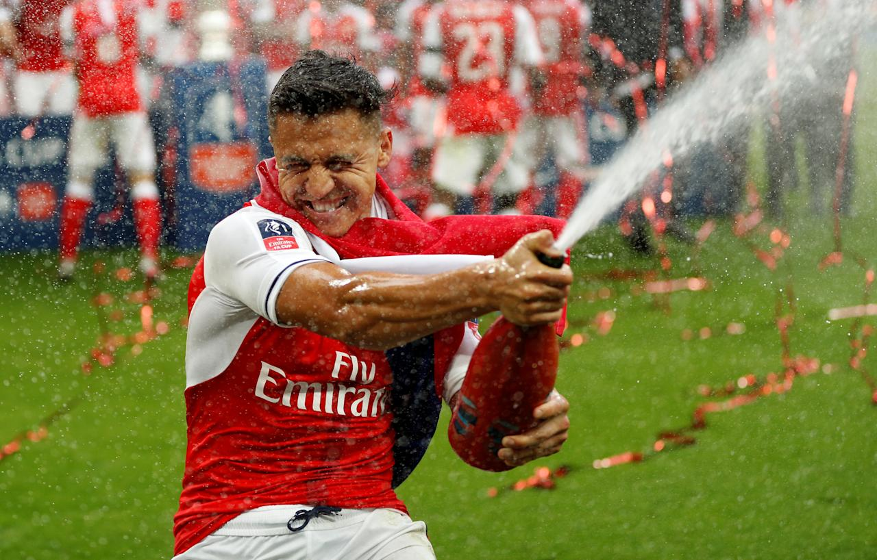 """Britain Soccer Football - Arsenal v Chelsea - FA Cup Final - Wembley Stadium - 27/5/17 Arsenal's Alexis Sanchez celebrates by spraying sparkling wine at the end of the match Action Images via Reuters / John Sibley EDITORIAL USE ONLY. No use with unauthorized audio, video, data, fixture lists, club/league logos or """"live"""" services. Online in-match use limited to 45 images, no video emulation. No use in betting, games or single club/league/player publications.  Please contact your account representative for further details."""