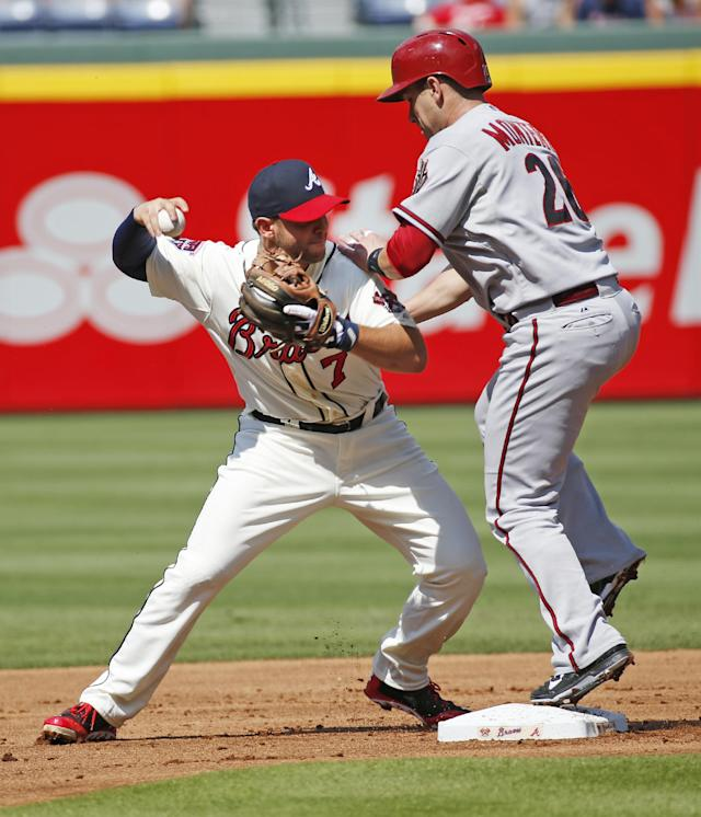 Atlanta Braves second baseman Tommy La Stella (7) collides with Arizona Diamondbacks' Miguel Montero (26) as he tries to throw out Martin Prado in the first inning of a baseball game in Atlanta, Saturday, July 5, 2014. Montero was out, and Prado was safe at first. (AP Photo/John Bazemore)