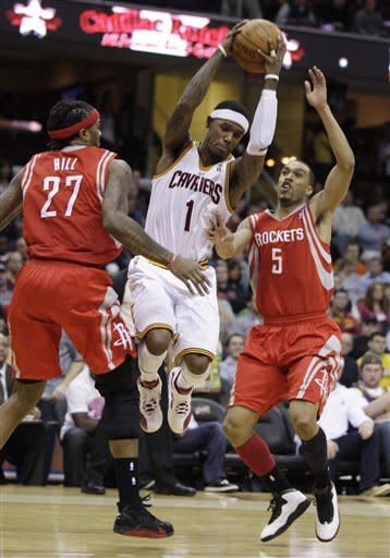 Cleveland Cavaliers' Daniel Gibson (1) jumps between Houston Rockets center Jordan Hill (27) and Courtney Lee (5) in the first quarter in an NBA basketball game Sunday, March 11, 2012, in Cleveland. (AP Photo/Tony Dejak)