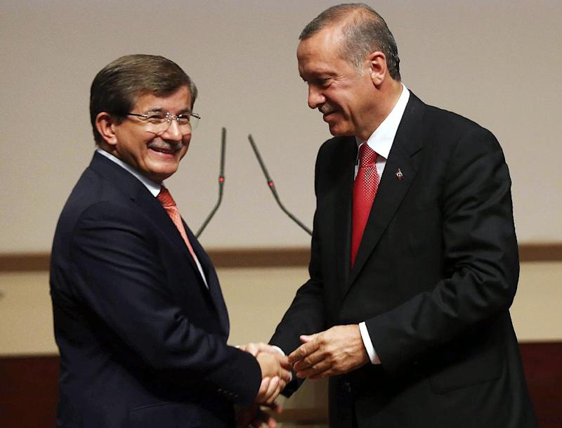 Turkey's president-elect Recep Tayyip Erdogan (R) shakes hands with Foreign Minister Ahmet Davutoglu after he announced Davutoglu as new chairman of his ruling AKP party and new prime minister, in Ankara on August 21, 2014