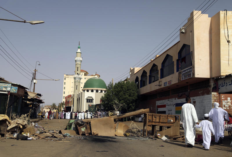 Sudanese men and a child headed to a mosque navigate a roadblock set by protesters on a main street in the Sudanese capital Khartoum to stop military vehicles from driving through the area on Wednesday, June 5, 2019. The death toll in Sudan amid a violent crackdown on pro-democracy protesters and the dispersal of their peaceful sit-in earlier this week in the capital climbed on Wednesday, protest organizers said. (AP Photo)