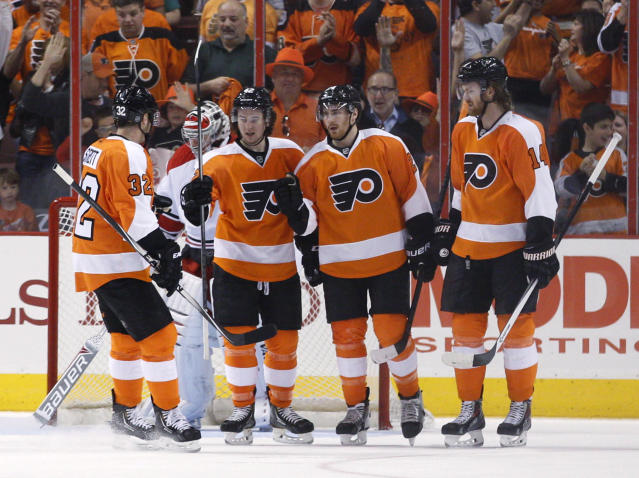 Philadelphia Flyers' Matt Read, center right, celebrates his goal on Carolina Hurricanes' Anton Khudobin, behind, with Mark Streit, left, of Switzerland; Jason Akeson, center left; and Sean Couturier, right, during the first period of an NHL hockey game, Sunday, April 13, 2014, in Philadelphia. (AP Photo/Chris Szagola)