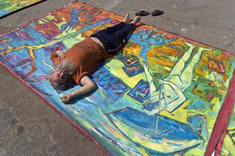 In this photo taken on April 4, 2013, Romanian artist Vasile Muresan, known as Murivale poses on one of his paintings in a parking lot, in Bucharest, Romania. The white-bearded painter can often be seen sitting on his colorful canvasses which he displays in the street followed by the street dogs which are his companions and also inspire his work. The 56-year-old, whose home city is Bistrita_the Transylvanian town associated with the legendary Count Dracula_ has been painting with passion since he was a teen, producing vivid works of Monaco, the streets of Paris, the hurly burly of the Romanian capital and huge colorful more abstract canvasses. (AP Photo/Vadim Ghirda)