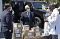 Vice President Mike Pence, center, speaks to staff members after delivering personal protective equipment to the Westminster Baldwin Park, Wednesday, May 20, 2020, in Orlando, Fla., as part of the initiative to deliver PPE to more than 15,000 nursing homes across America. Looking on is Florida Gov. Ron DeSantis, left. Pence is also scheduled to participate in a roundtable discussion with hospitality and tourism industry leaders to discuss their plans for re-opening during the coronavirus outbreak. (AP Photo/Chris O'Meara)