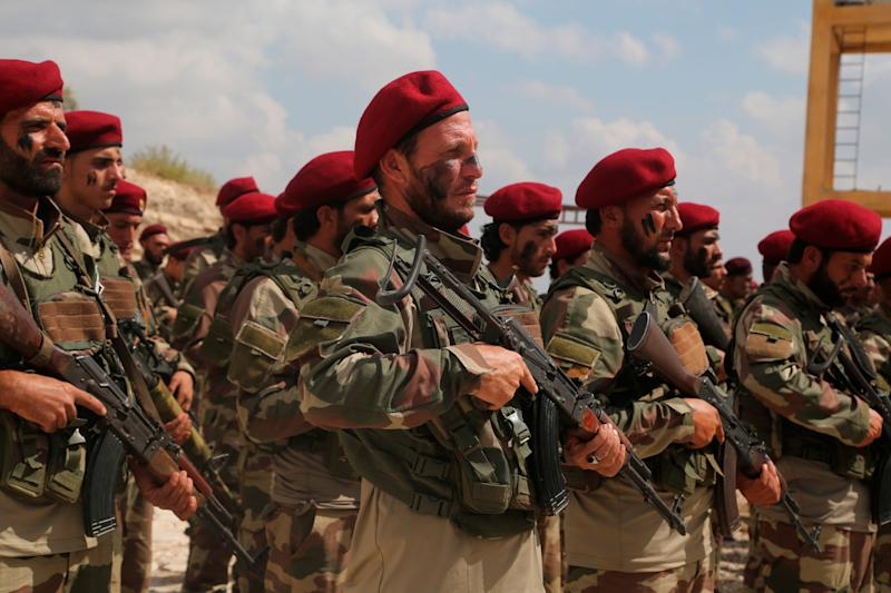 Turkish-backed forces from the Free Syrian Army prepare for an incursion targeting Syrian Kurdish fighters Oct. 7 near Azaz, Syria.
