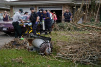 Paramedic J.T. Lebouef of Acadian Ambulance service, left, and others move a patient to an ambulance at a home damaged by Hurricane Ida, Friday, Sept. 3, 2021, in Houma, La. (AP Photo/John Locher)