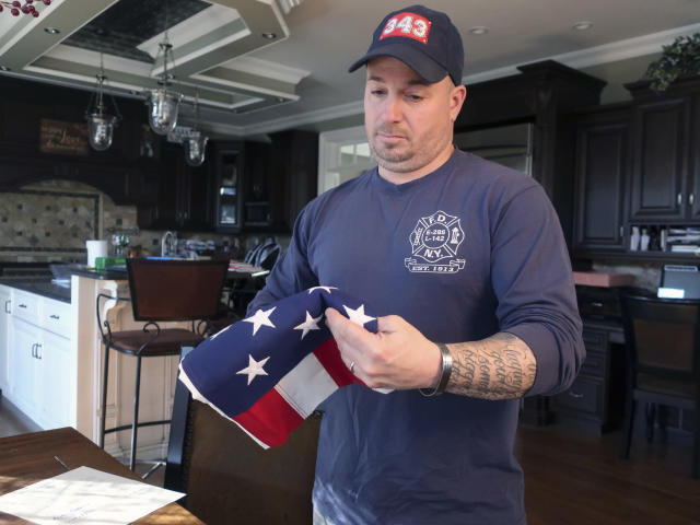 In this January 14, 2019 photo retired firefighter Lt. Michael O'Connell looks at an American flag at his home in Westbury, New York. A Memorial Glade will soon open at the 9/11 Memorial to honor first responders who are sick or who have died from exposure to toxins at the World Trade Center after the 9/11 attacks. O'Connell suffers from sarcoidosis, an inflammatory disease, from his rescue and recovery work after the 9/11 terror attacks. (AP Photo/Ted Shaffrey)