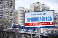 """A monorail car rolls near a gait billboard reading """"You're over 60! Get vaccinated immediately!"""" in Moscow, Russia, Sunday, April 4, 2021. To boost the demand, officials in Moscow this week started offering 1,000-ruble ($13) coupons to people over 60 for getting vaccinated. So far, the incentive hasn't elicited a lot of enthusiasm among elderly Muscovites. While some told the AP the initiative was helpful for those living off a relatively small pension, others complained about difficulties registering online to get the coupons or finding grocery stores where they could be used. (AP Photo/Alexander Zemlianichenko)"""