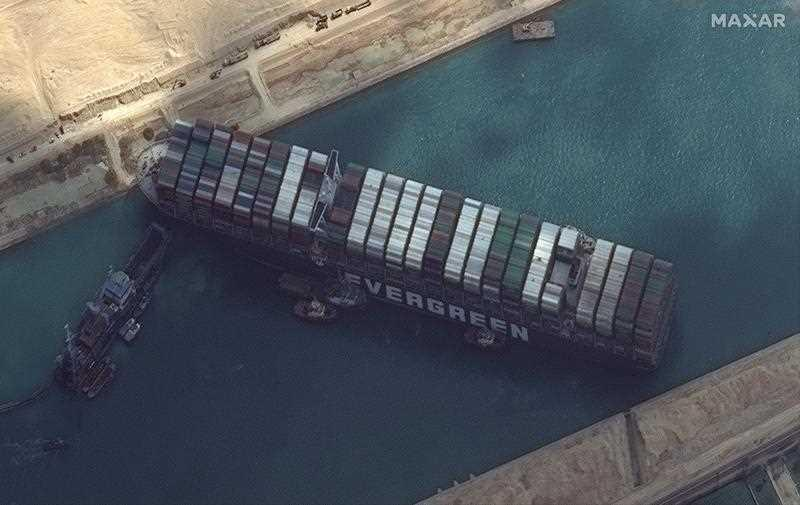 A handout satellite image made available by MAXAR Technologies shows multiple tug boats positioned alongside the 'Ever Given' and dredging operations in progress, in the Suez Canal, Egypt.