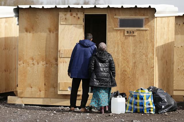 Kurdish migrant family stands at the door of their wood shelter in a refugee camp in Grande-Synthe, near Dunkirk