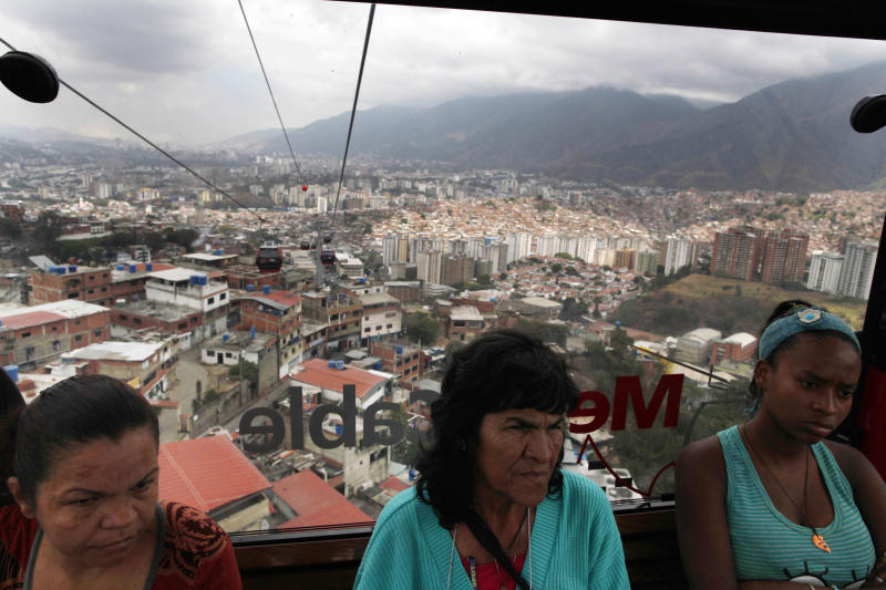 In this March 14, 2013 photo, Marisol Lezaman, left, Teresa Montilla, center, and Yetcimar Rosales, right, commute in a cable car that moves above homes in Caracas, Venezuela. On their daily cable car rides to and from home in Venezuela's capital, commuters soar in a bubble of safety far above the deadly, trash-strewn streets below. Amid a list of woes, including double-digit inflation and crumbling infrastructure, rampant crime is seen by many as the main failing of the late President Hugo Chavez's government, and one that a whole swath of this shell-shocked country has lost hope of correcting. (AP Photo/Rodrigo Abd)