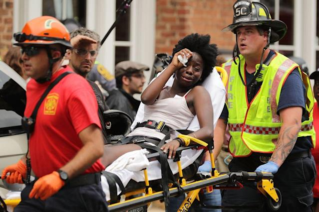 Rescue workers move victims on stretchers after car plowed through a crowd of counter-demonstrators marching through the downtown shopping district Aug. 12, 2017 in Charlottesville, Va. (Photo: Chip Somodevilla/Getty Images)