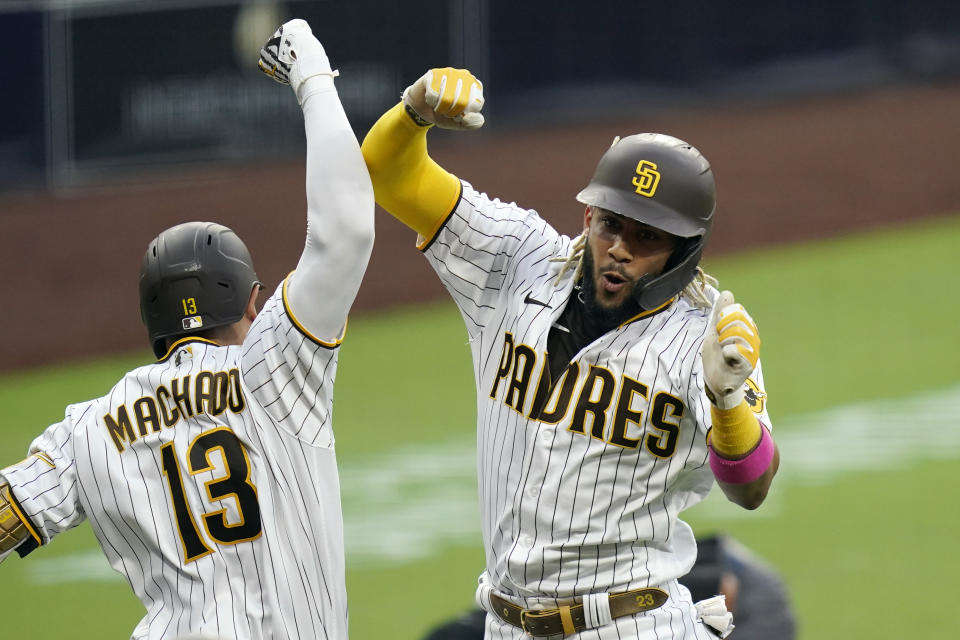 San Diego Padres' Fernando Tatis Jr., right, reacts with teammate Manny Machado (13) after hitting a home run during the third inning of a baseball game against the Texas Rangers, Wednesday, Aug. 19, 2020, in San Diego. (AP Photo/Gregory Bull)
