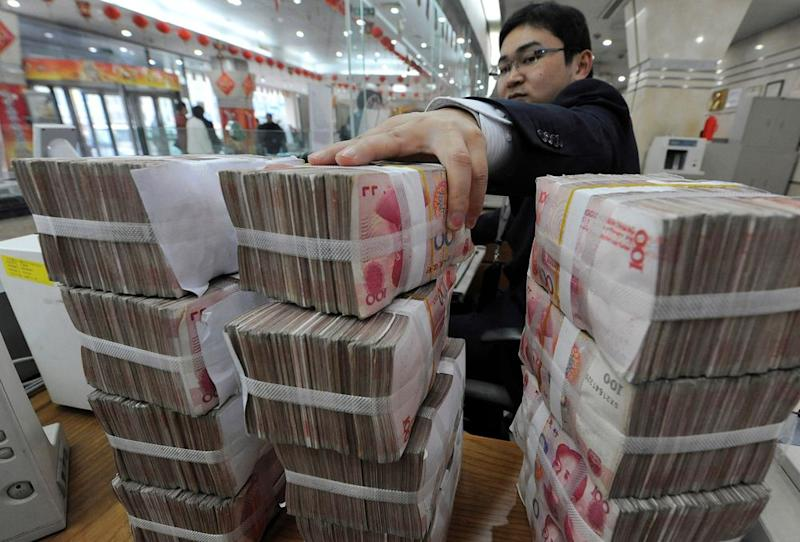 An employee counts Chinese yuan banknotes at a Bank of China branch in Hefei, Anhui province March 10, 2010. — Reuters pic