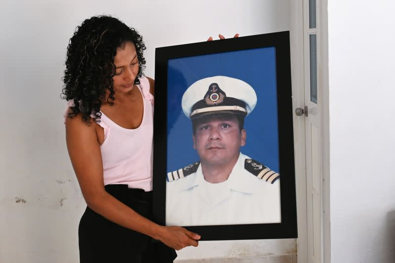 Claudia Patricia Fortich, widow of late oil tanker captain Jaime Herrera Orozco who was murdered on his ship while anchored off Venezuela, holds a picture of her husband at her home, in Cartagena