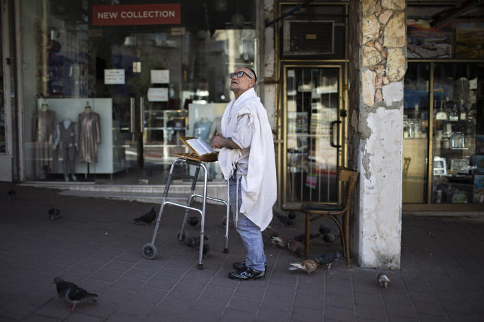 Image: A man prays next to his house in Bnei Brak last week. (Oded Balilty / AP)