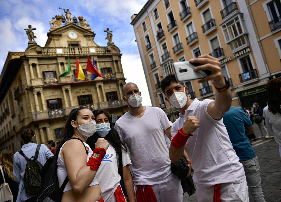 Residents, wearing white clothes and traditional red scarves, take a selfie in front of the City Hall, on the day the ''txupinazo'' would usually take place to start the famous San Fermin festival, which was due canceled this year by the conoravirus, in Pamplona, northern Spain, Monday, July 6, 2020. (AP Photo/Alvaro Barrientos)