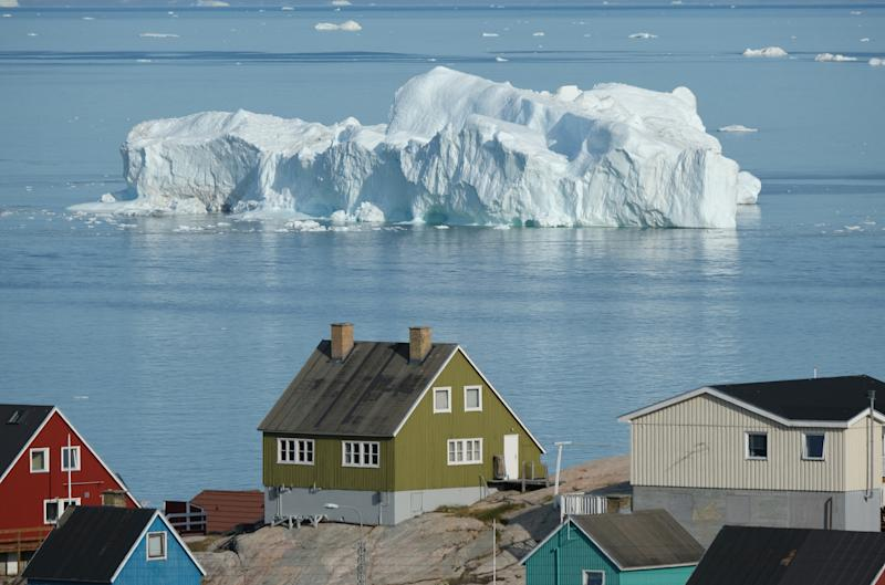 An iceberg floats in Disko Bay behind houses during unseasonably warm weather in Ilulissat, Greenland. (Photo: Sean Gallup/Getty Images)