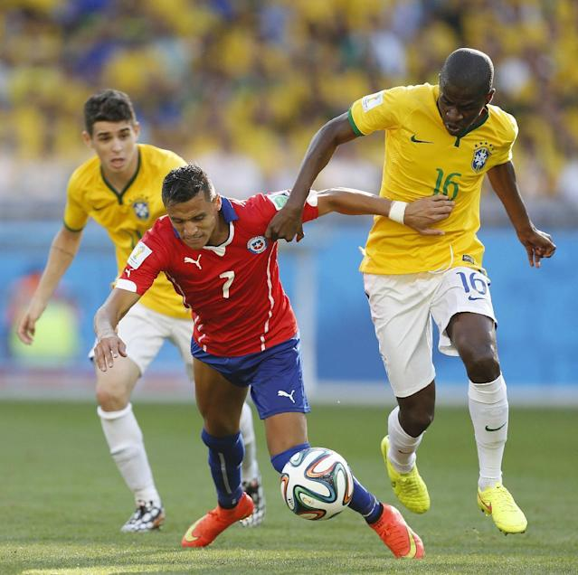 Chile's Alexis Sanchez, center, fights for the ball with Brazil's Oscar, left, and Brazil's Ramires during the World Cup round of 16 soccer match between Brazil and Chile at the Mineirao Stadium in Belo Horizonte, Brazil, Saturday, June 28, 2014. (AP Photo/Frank Augstein)