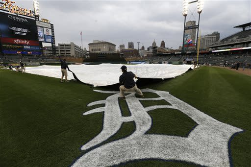 Members of the Detroit Tigers grounds crew move the rain tarp into place before a baseball game against the Kansas City Royals in Detroit, Tuesday, April 23, 2013. (AP Photo/Carlos Osorio)