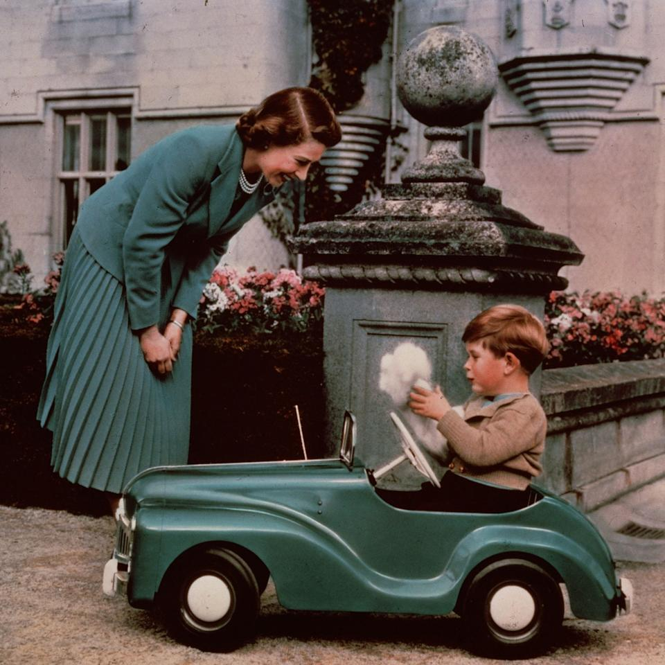 28th September 1952: Queen Elizabeth watching her son Prince Charles playing in his toy car while at Balmoral - Lisa Sheridan/Hulton Royals Collection