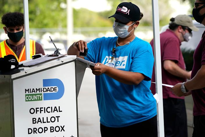 Election workers stamp the ballots dropped by voters before putting them in the official ballot drop box (AP).
