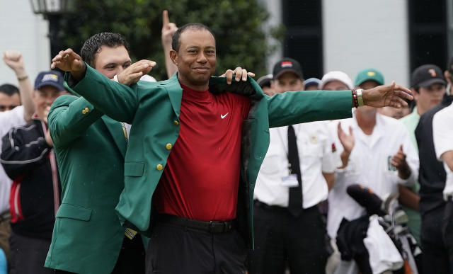Patrick Reed helps Tiger Woods with his green jacket after Woods won the Masters golf tournament Sunday, April 14, 2019, in Augusta, Ga. (AP Photo/David J. Phillip)