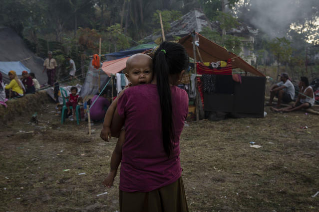 <p>An Indonesian woman carrying a baby at a temporary shelter in Pemenang on Aug. 7, 2018 in Lombok Island, Indonesia. (Photo: Ulet Ifansasti/Getty Images) </p>