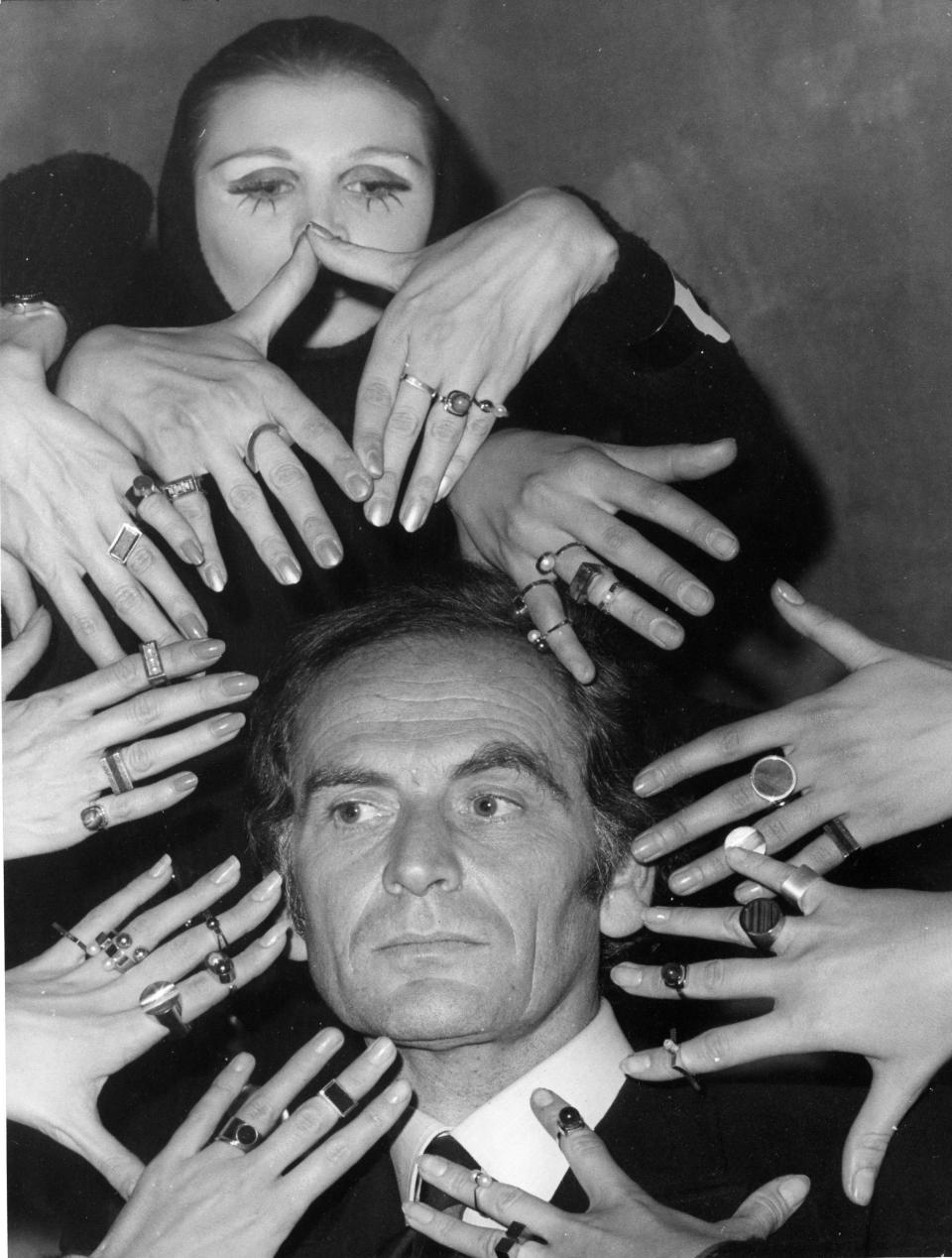 FILE - In this Sept. 19, 1969 file photo, French fashion designer Pierre Cardin's face is framed by 10 hands of models like a sculptur of goddess Siva ornamented with a collection of rings designed by Cardin from his latest jewelery collection, in Paris, France.France's Academy of Fine Arts says Pierre Cardin, the French designer whose Space Age style was among the iconic looks of 20th-century fashion, has died at 98.(AP Photo, File)